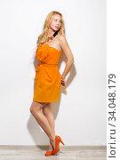 Купить «Fashion model girl full-length portrait in orange dress and modern accessories.», фото № 34048179, снято 13 марта 2016 г. (c) Nataliia Zhekova / Фотобанк Лори