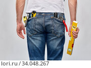 Купить «man with level and working tools in pockets», фото № 34048267, снято 21 ноября 2019 г. (c) Syda Productions / Фотобанк Лори