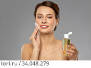 Купить «young woman with toner or cleanser and cotton pad», фото № 34048279, снято 30 ноября 2019 г. (c) Syda Productions / Фотобанк Лори