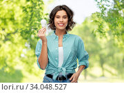 smiling woman holding energy saving lighting bulb. Стоковое фото, фотограф Syda Productions / Фотобанк Лори