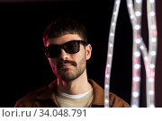 man in sunglasses over neon lights at nightclub. Стоковое фото, фотограф Syda Productions / Фотобанк Лори