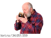 Senior man drinking from transparent brown cup, isolated on white background. Стоковое фото, фотограф Zoonar.com/Serghei Starus / easy Fotostock / Фотобанк Лори