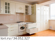 Modern classic spacioius cream colored kitchen, some drawers are open. Стоковое фото, фотограф Zoonar.com/Serghei Starus / easy Fotostock / Фотобанк Лори