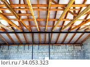 Купить «Double roof rafters. Construction of second floor inside», фото № 34053323, снято 30 июня 2019 г. (c) Евгений Ткачёв / Фотобанк Лори