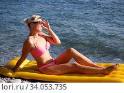 Happy woman in sunglasses sitting on air mattress by the sea. Стоковое фото, фотограф Константин Сиятский / Фотобанк Лори
