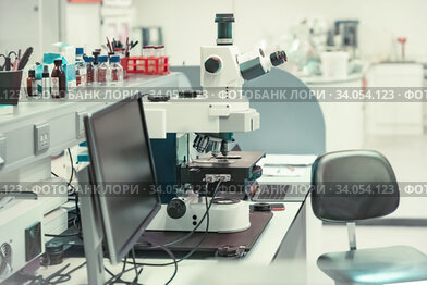 Microscope with metal lens at laboratory for developing vaccines against coronavirus