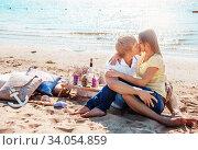 Купить «happy young couple enjoying picnic on the beach and have good time on summer», фото № 34054859, снято 6 сентября 2014 г. (c) Nataliia Zhekova / Фотобанк Лори