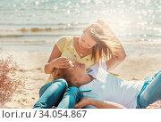 Купить «happy young couple enjoying picnic on the beach and have good time on summer day», фото № 34054867, снято 6 сентября 2014 г. (c) Nataliia Zhekova / Фотобанк Лори