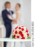 Купить «Wedding bridal bouquet with red and white roses on the table against the background of the bride and groom», фото № 34054883, снято 1 ноября 2014 г. (c) Nataliia Zhekova / Фотобанк Лори