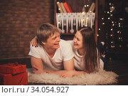 Beautiful couple in love lay on the floor at Christmas. Стоковое фото, фотограф Nataliia Zhekova / Фотобанк Лори