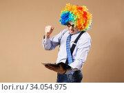 Купить «Portrait of business man in clown wig using a tablet to access the internet», фото № 34054975, снято 28 февраля 2016 г. (c) Nataliia Zhekova / Фотобанк Лори