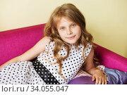 portrait of a lovely little girl in polka dot dress resting on purple sofa. Стоковое фото, фотограф Nataliia Zhekova / Фотобанк Лори