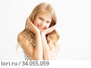 Lovely frisky little girl in a polka-dot dress against a white background. Стоковое фото, фотограф Nataliia Zhekova / Фотобанк Лори