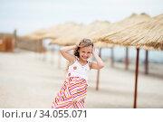 Portrait of a beautiful little girl in a sundress standing on a golden beach. Стоковое фото, фотограф Nataliia Zhekova / Фотобанк Лори
