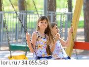 Две девочки качаются на качелях в городском парке. Стоковое фото, фотограф Иванов Алексей / Фотобанк Лори