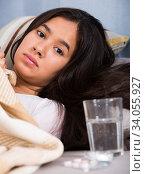 Sick and sad young female lying at sofa. Стоковое фото, фотограф Яков Филимонов / Фотобанк Лори