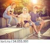 Teenagers using phones and chatting on streets in summer. Стоковое фото, фотограф Яков Филимонов / Фотобанк Лори