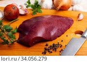 Купить «Raw pork liver on wooden surface with garlic and greens», фото № 34056279, снято 2 июля 2020 г. (c) Яков Филимонов / Фотобанк Лори