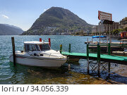 Empty taxi boat moored to a pier on lake Lugano on a spring sunny day. View of the San Salvatore mountain. Canton of Ticino, Switzerland, Europe. (2018 год). Редакционное фото, фотограф Bala-Kate / Фотобанк Лори