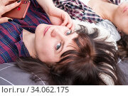 Купить «Portrait of a woman, head on a pillow, medium-length hair, listening to music from the phone», фото № 34062175, снято 4 января 2020 г. (c) Катерина Белякина / Фотобанк Лори