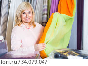 Купить «Mature woman customer choosing color curtains», фото № 34079047, снято 17 января 2018 г. (c) Яков Филимонов / Фотобанк Лори