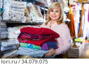Positive mature woman choosing cotton bedcover in the textile shop. Стоковое фото, фотограф Яков Филимонов / Фотобанк Лори
