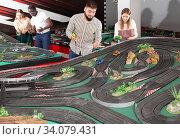 Two teams from people play slot car racing game. Стоковое фото, фотограф Яков Филимонов / Фотобанк Лори