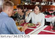 Two girls with male friend in restaurant. Стоковое фото, фотограф Яков Филимонов / Фотобанк Лори