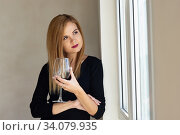 Девушка задумчиво стоит у окна с бокалом красного вина. Стоковое фото, фотограф Иванов Алексей / Фотобанк Лори