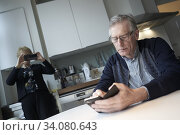 Senior woman taking smartphone photo of man using smartphone at breakfast table in kitchen. Стоковое фото, фотограф Egerland Productions / age Fotostock / Фотобанк Лори