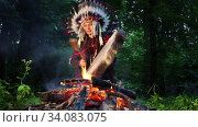 Shaman woman in native American Indian headdress drumming by the fire in forest at dusk. Стоковое видео, видеограф Алексей Кузнецов / Фотобанк Лори