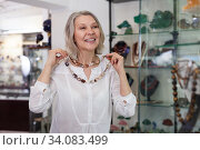 Woman trying on a gemstone necklace and earrings at a jewelry store. Стоковое фото, фотограф Яков Филимонов / Фотобанк Лори