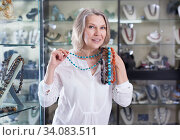 Woman trying on a turquoise necklace and earrings at a jewelry store. Стоковое фото, фотограф Яков Филимонов / Фотобанк Лори
