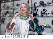 Woman trying on a aventurine necklace and earrings at a jewelry store. Стоковое фото, фотограф Яков Филимонов / Фотобанк Лори
