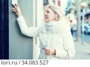 Mature woman is visiting somebody with note with address. Стоковое фото, фотограф Яков Филимонов / Фотобанк Лори
