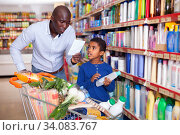 Young African American man with cute preteen son choosing household detergents in store together. Стоковое фото, фотограф Яков Филимонов / Фотобанк Лори