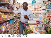 Купить «Jolly African American man with purchases», фото № 34083775, снято 15 апреля 2019 г. (c) Яков Филимонов / Фотобанк Лори