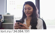 Professional businesswoman using smartphone while sitting on her desk in office in slow motion. Стоковое видео, агентство Wavebreak Media / Фотобанк Лори