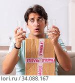 Купить «Man opening fragile parcel ordered from internet», фото № 34088167, снято 4 июля 2018 г. (c) Elnur / Фотобанк Лори
