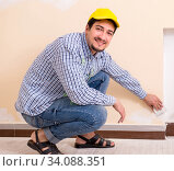 Купить «Young contractor sanding wall down with sandpaper», фото № 34088351, снято 3 мая 2018 г. (c) Elnur / Фотобанк Лори