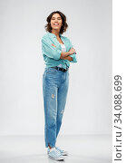 smiling young woman in turquoise shirt and jeans. Стоковое фото, фотограф Syda Productions / Фотобанк Лори