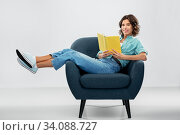happy young woman in armchair reading book. Стоковое фото, фотограф Syda Productions / Фотобанк Лори