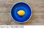 Bright yellow lemon on a blue plate on a wooden tabletop. Стоковое фото, фотограф Евгений Харитонов / Фотобанк Лори