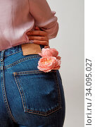 Купить «Young girl wearing of jean pants and pink shirt from back with natural flowers roses in a pocket on a gray background, copy space. Concept of Woman's or Mother's Day.», фото № 34095027, снято 3 июля 2020 г. (c) easy Fotostock / Фотобанк Лори