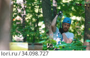 Купить «A man in helmet having a rope adventure in the forest with full insurance - coming down using his insurance belt», видеоролик № 34098727, снято 14 июля 2020 г. (c) Константин Шишкин / Фотобанк Лори