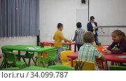 Купить «Happy pupils chattering sitting at lesson in elementary school», видеоролик № 34099787, снято 29 января 2020 г. (c) Яков Филимонов / Фотобанк Лори