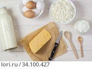 Купить «Яйца, творог, сметана, молоко и сыр на белом деревянном столе. Деревенские продукты», фото № 34100427, снято 10 мая 2020 г. (c) Наталья Гармашева / Фотобанк Лори