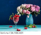 Спелая черешня и ваза с цветами на синем деревянном столе. Лето. Стоковое фото, фотограф Наталья Гармашева / Фотобанк Лори