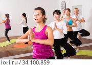 Group of young women training yoga positions in modern yoga studio. Стоковое фото, фотограф Яков Филимонов / Фотобанк Лори