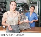 Купить «Dissatisfied woman customer of dry cleaning», фото № 34100899, снято 9 мая 2018 г. (c) Яков Филимонов / Фотобанк Лори